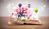 Aufgeschlagenes Buch mit fliegenden 3D-Buchstaben auf Betongrund