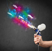 Photo Worker with airbrush and colorful abstract clouds and balloons