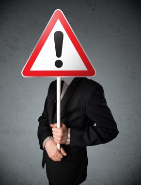 Businessman holding a red traffic triangle warning sign in front of his head stock vector