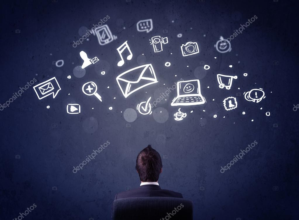 Businessman in chair with multimedia icons over his head