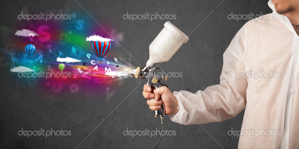 Worker with airbrush and colorful abstract clouds and balloons