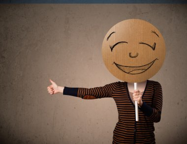 Young woman holding a smiley face board