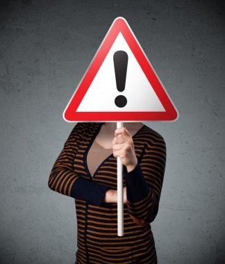 Young woman holding a red traffic triangle warning sign in front of her head stock vector