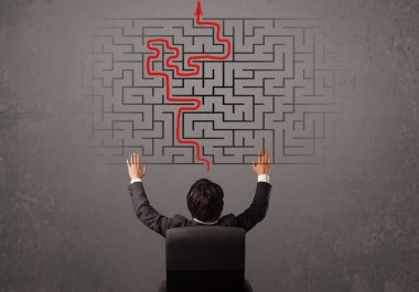 Business man looking at a maze and the way out