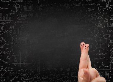 Happy finger smileys with black chalkboard in background