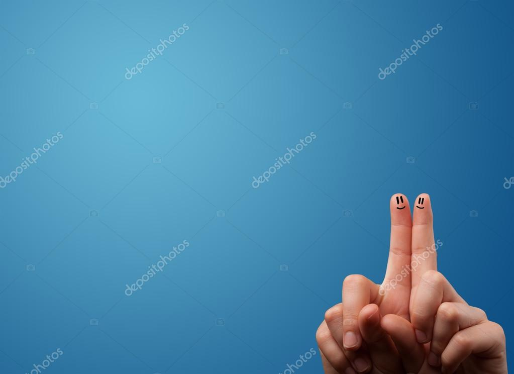 Happy smiley face fingers looking at empty blue background copy
