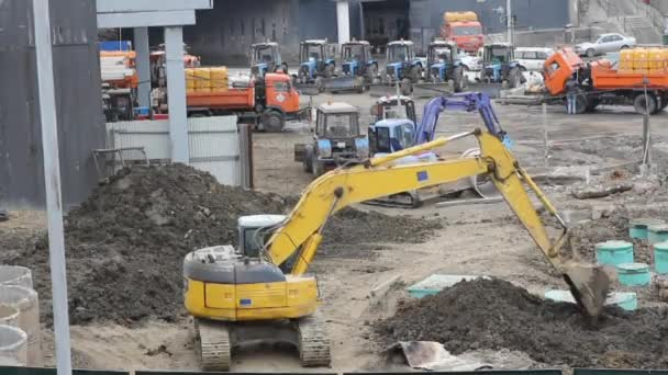 yellow track-type excavator digs the ground