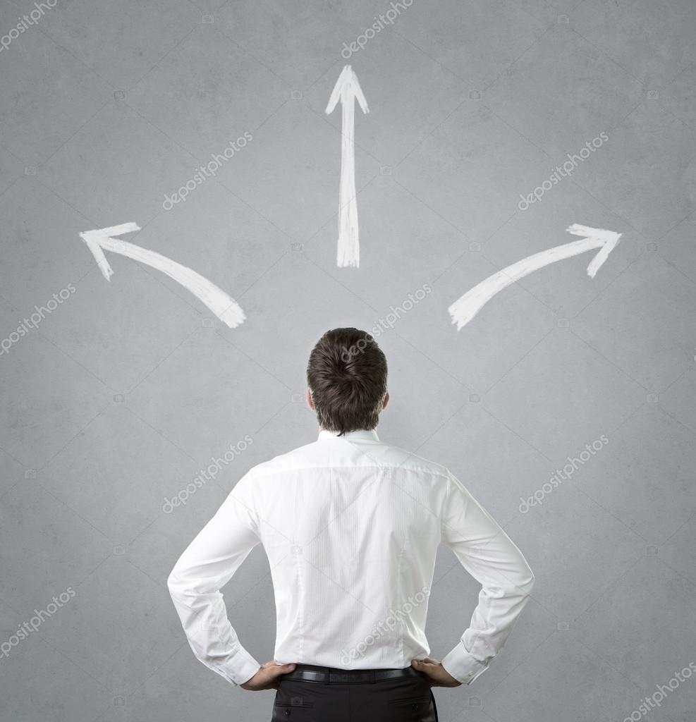 Businessman looking at chalk drawn arrows