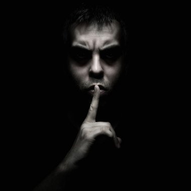 Evil man gesturing silence, quiet isolated on black background stock vector