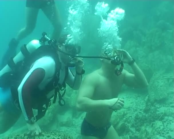 Swimmer breathing from divers regulator underwater diving video