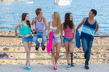 group of diverse mixed race teens hanging out at beach.