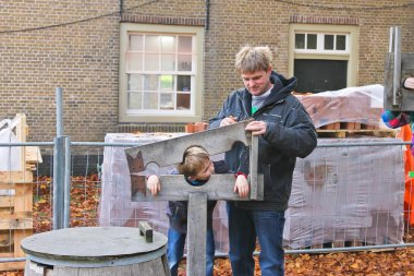Father shows his son device pillory in the Dutch suburb. Netherl