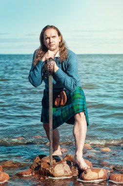 Scottish man with sword at the sea