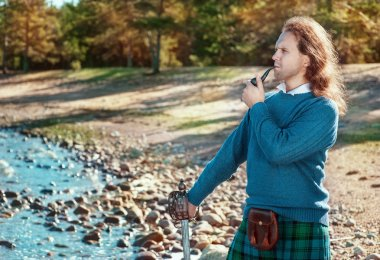 Handsome scottish man with sword and pipe