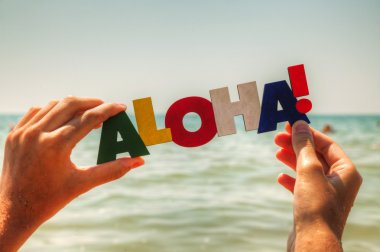 Female's hand holding colorful word 'Aloha'