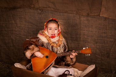Beautiful russian girl in a shawl sitting in a cart