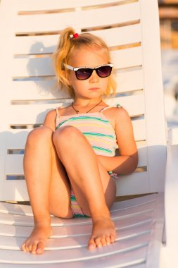 Adorable kid in sunglasses sunbathing on a lounge on a beach stock vector