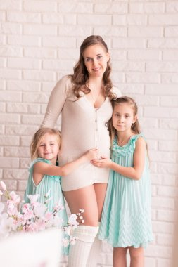 Beautiful pregnant woman with two daughters