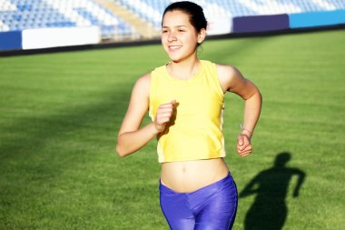 Beautiful teenage sport girl running on the stadium grass