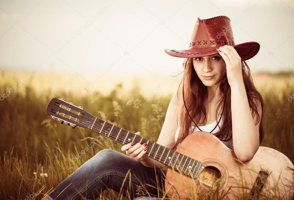 Woman with guitar at spring grass