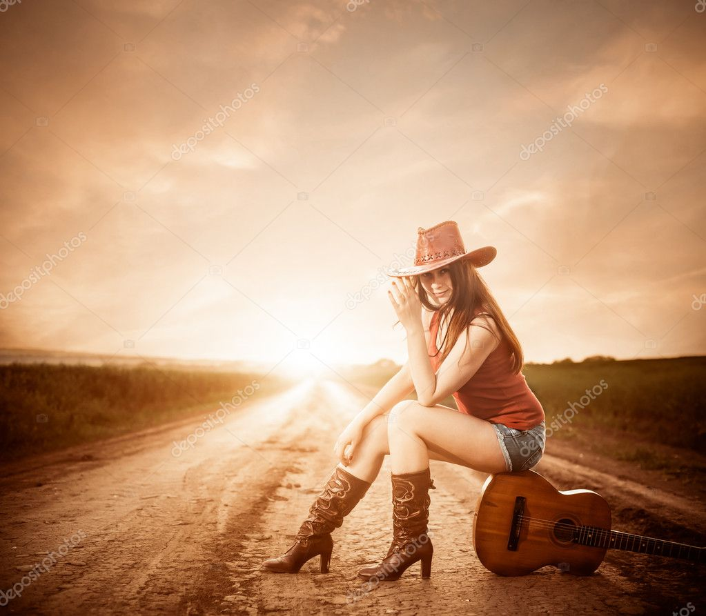 Stylish cowgirl on a sunset road