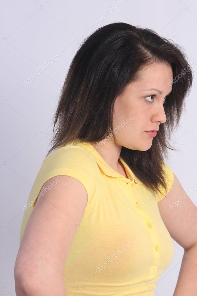 Lovely young brunette in a yellow shirt against a light colored background.