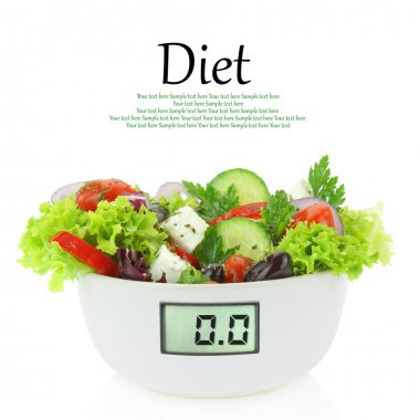 Diet meal. Vegetables salad in a bowl with digital weight scale