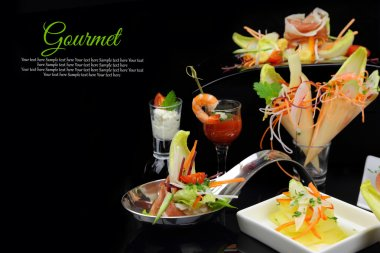 Various gourmet dishes with copy-space on black background