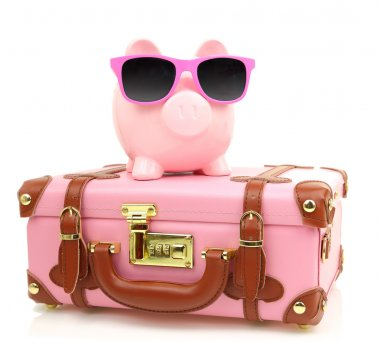 Pink suitcase with piggy bank in sunglasses isolated