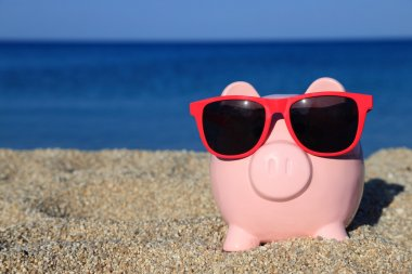 Summer piggy bank on the beach