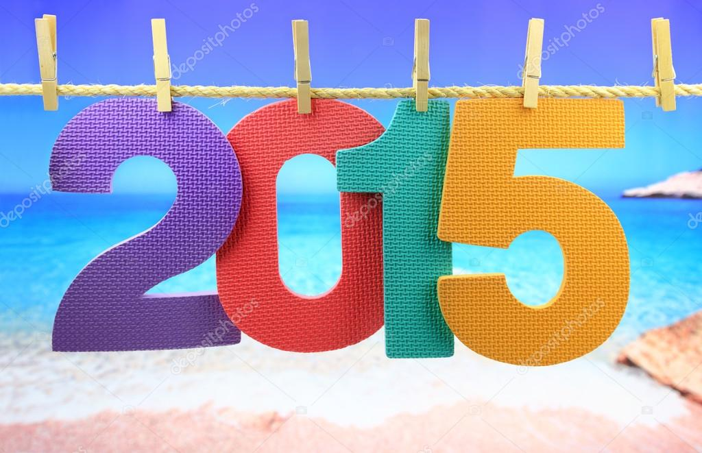 Colorful number 2015 year hanging on a rope in front of the sea