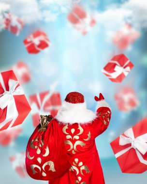 Santa Claus standing and doing magic. Gift boxes falling down ar