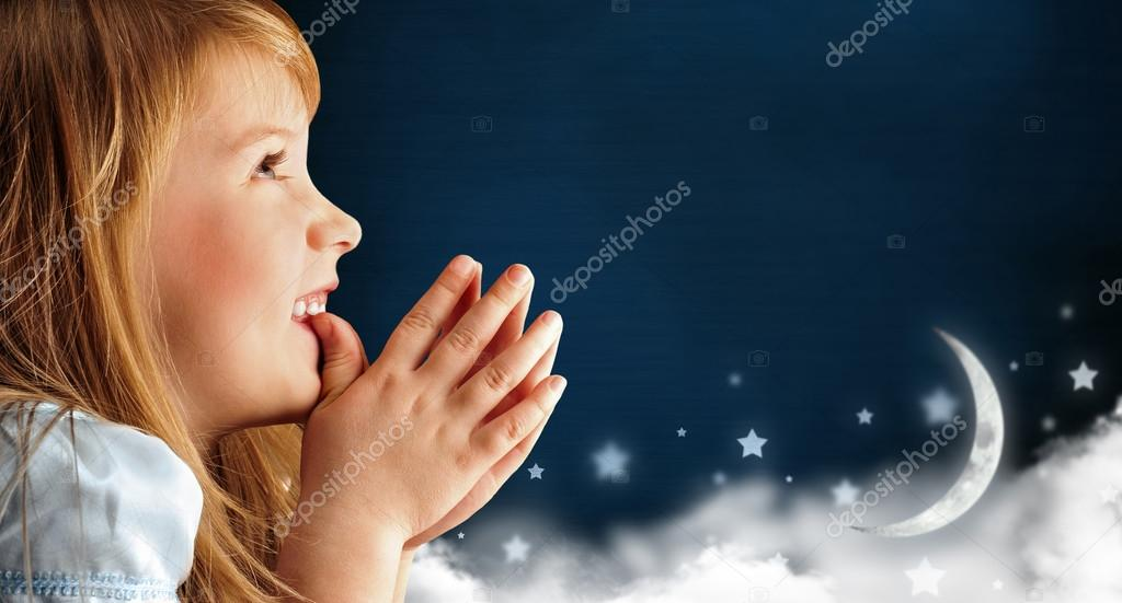 Portrait of little smiling praying girl in blue dress against da