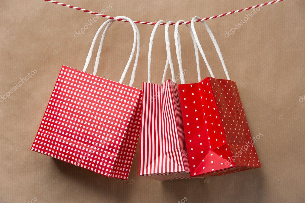 32e4e92fa5 Κόκκινο δώρο πακέτο χάρτινες τσάντες που κρέμεται από μια κορδέλα. Παλαιόν  Ιστορικόν καφετιού εγγράφου — Εικόνα από ...