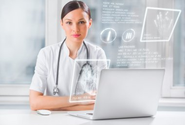 Doctor with hightech computer screen viewing patient data