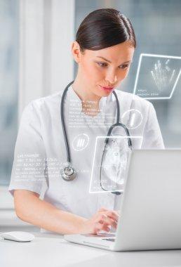 Pretty female medicine doctor working with modern computer inter