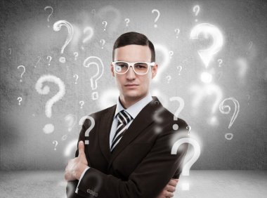 Handsome business man with question marks above his head