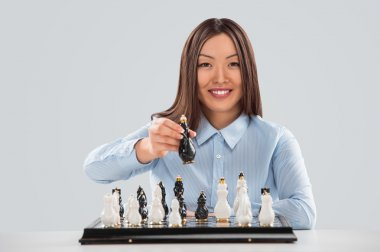 Closeup of a young woman holding chess piece and planning next step