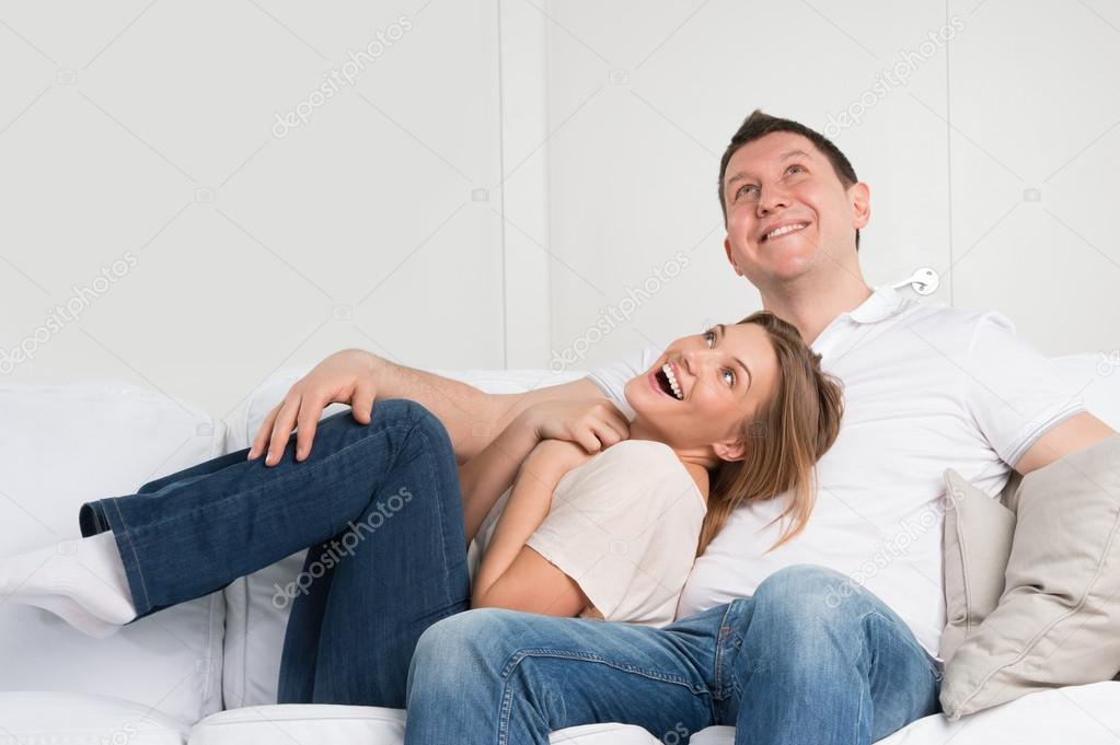 Young couple on the sofa in love planning future and having fun
