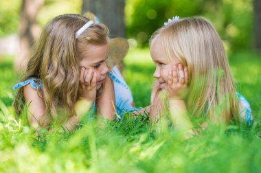 Two little cute girls on lawn in the park