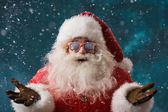 Fotografie Santa Claus wearing sunglasses dancing outdoors at North Pole