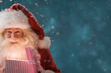 Santa Claus opening gift box outdoors at North Pole