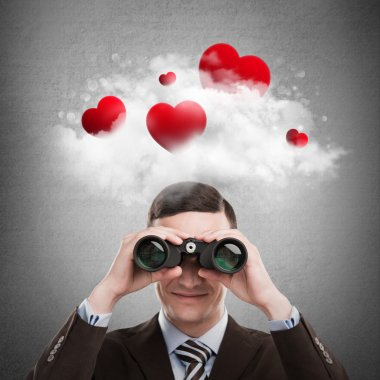 Red hearts flying in cloud overhead of man looking through binoculars.