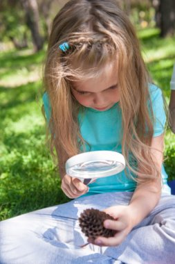 Little girl exploring the cone through the magnifying glass outdoors