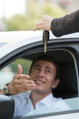 Salesman handing over keys car to businessman