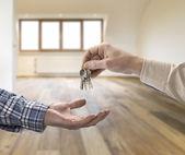 Fotografia Chiave di casa dando agente immobiliare acquirente nella stanza vuota