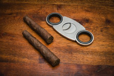 Italy, italian cigars (toscani) and a cigars cutter on a wooden table
