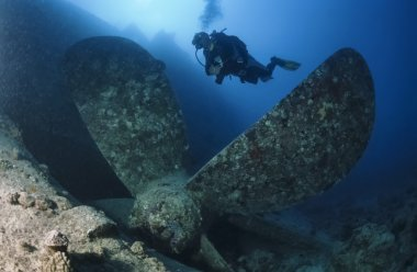 SUDAN, Red Sea, U.W. photo, Umbria wreck, a diver close to one of the propellers of the sunken ship