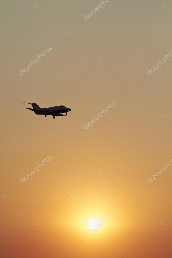 Executive jet flying in the sky at sunset