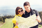 Fotografie Young couple with map in mountains